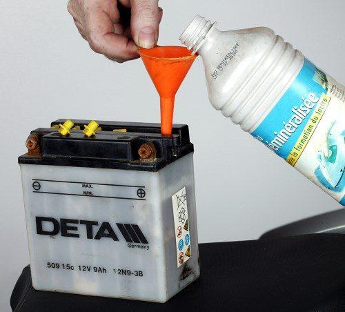 Remplissage d'une batterie de moto avec de l'eau démineralisée
