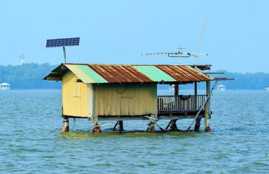 Une maison isolée dans l'eau avec un panneau solaire