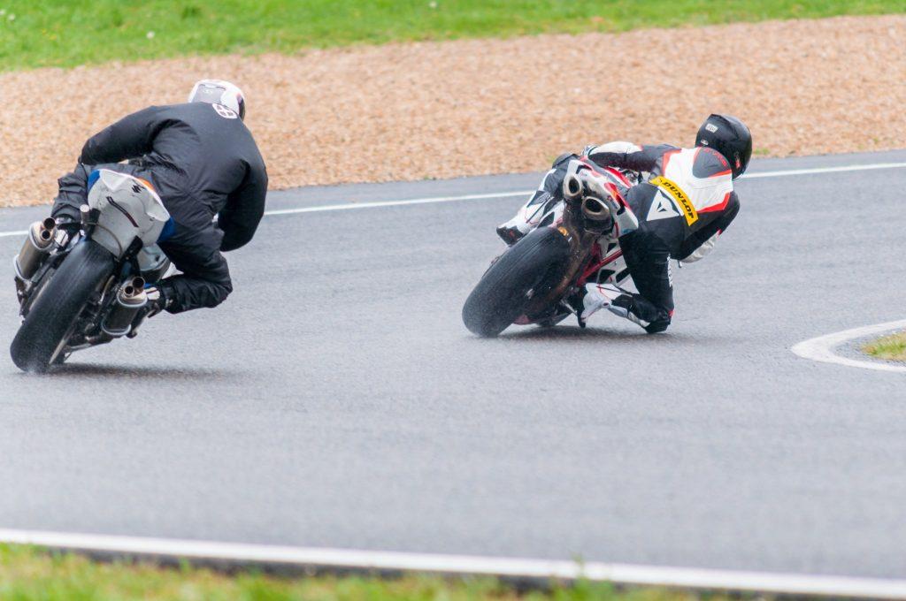 Deux pilotes de moto sur le circuit Carole sous la pluie en posant le genou
