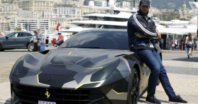 GMK qui pose à côté de sa Ferrari F12 Berlinetta
