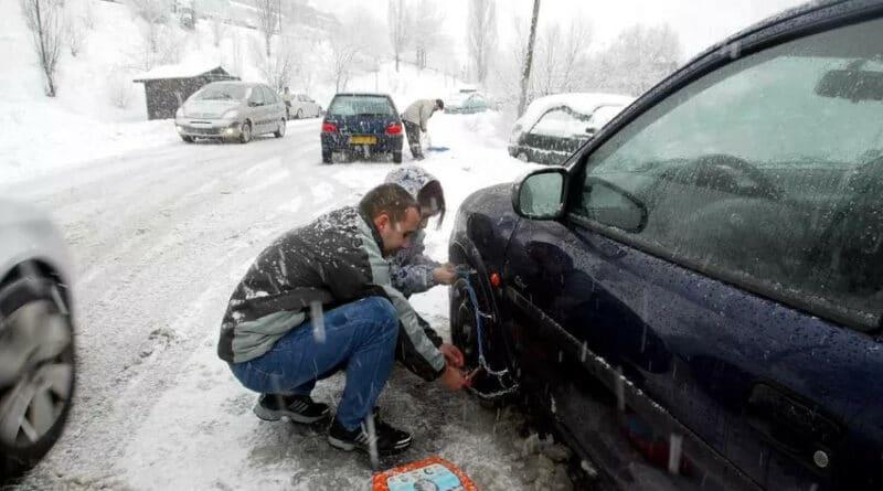 Un automobiliste monte des chaines sur sa voiture bloquée dans la neige