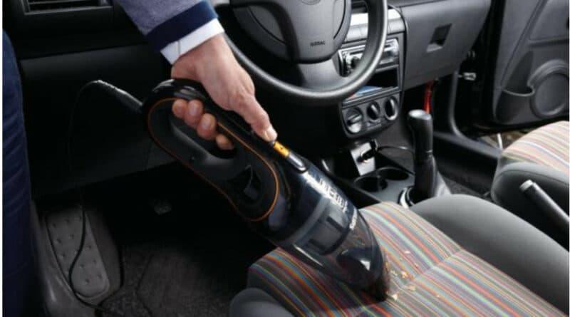 Un aspirateur portable qui nettoie un siège de voiture